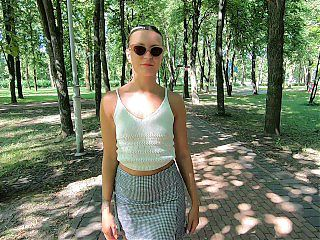 Public flashing.A young slut shows her tits and takes off her panties in a city park.